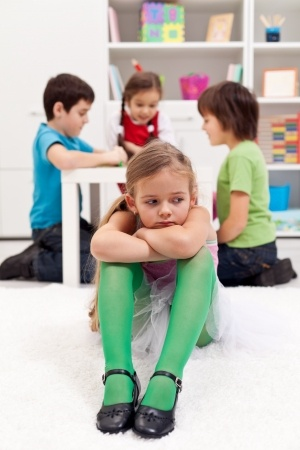 17405936 - sad little girl sitting excluded by the other kids