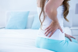 44785944 - attractive woman with back pain at home in the bedroom
