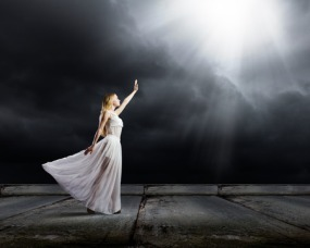 33119481 - young woman in in darkness reaching to sun light