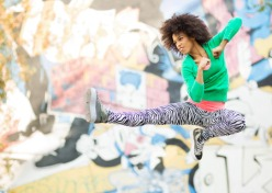 32868082 - young woman kicking in mid air