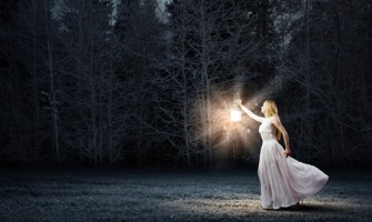32702468 - young woman with lantern walking in dark forest