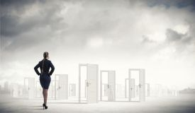 47912357 - businesswoman standing in front of opened doors and making decision