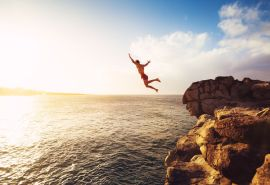 48837246 - cliff jumping into the ocean at sunset, summer fun lifestyle