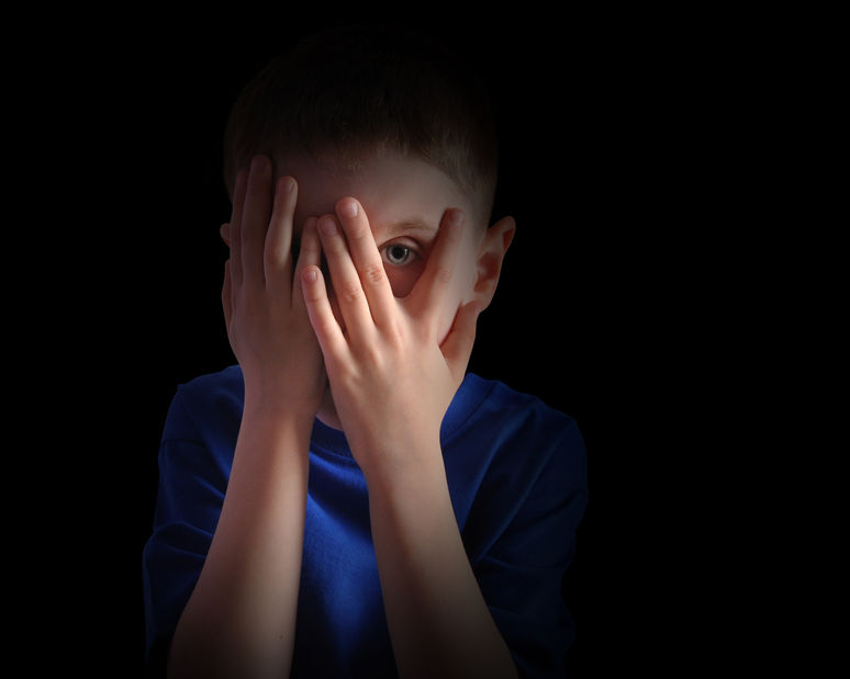 28469896 - a child is hiding his eyes in the dark and looks scared or upset.