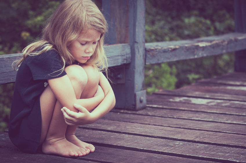 Portrait of sad blond little girl sitting on the bridge