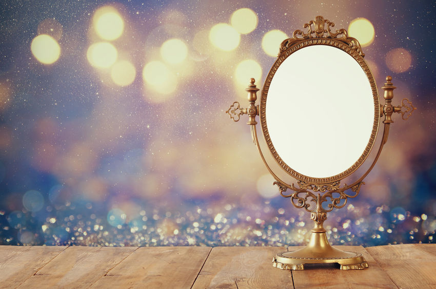 Old vintage oval mirror standing on wooden table