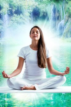 Attractive young woman in white meditating at lake.