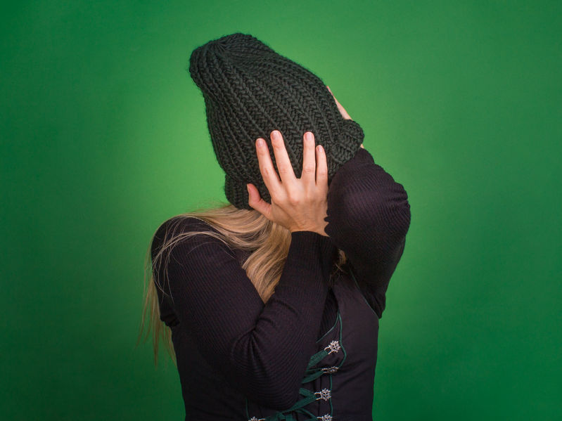The woman covers her face with a knitted hat and turns away