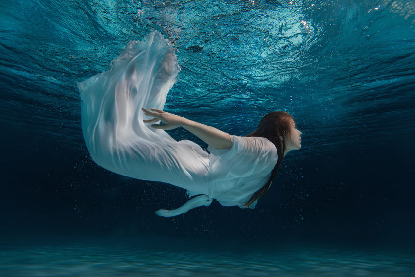 Woman in a white dress under water.