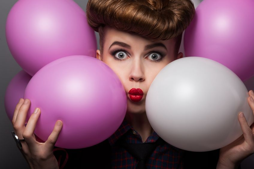16854815 - funny young woman with colorful air balloons enjoying