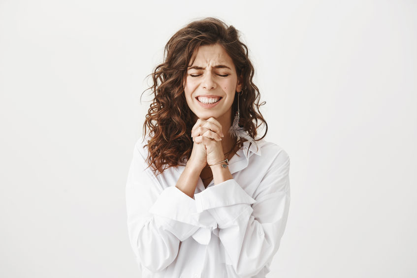 Studio shot of worried and upset caucasian woman holding hands in pray near chin, squeezing it tight and begging for something, smiling nervously and standing with closed eyes over gray background
